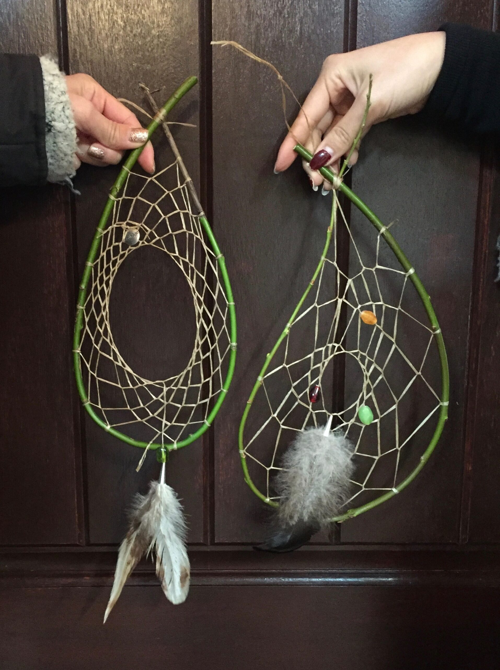 Two hands each holding dream catchers photo